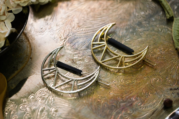 One silver and one gold crescent moon hair clip.