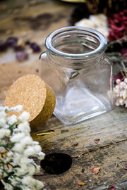 Clear square apothecary jar with cork off.