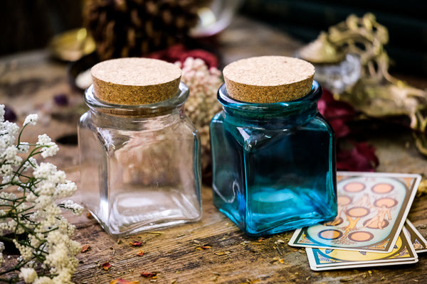 One clear and one blue apothecary jar on display with corks.