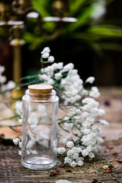 Clear tall round glass jar with cork on display next to babies breath.