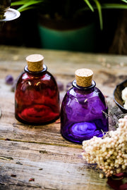 One red and one purple apothecary jar with corks displayed with dried flowers.