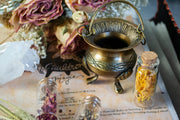 Small brass cauldron displayed with flowers and herb vials.