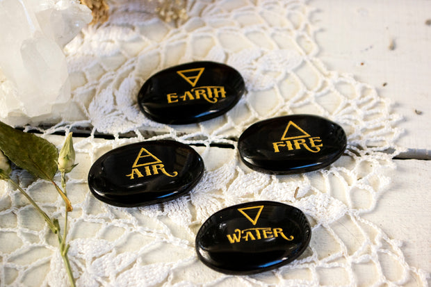 Four black agate stones with Earth, Air, Wind and Fire written on one of each of them.