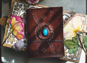 Front cover of the leather journal with stone mounted in the center.