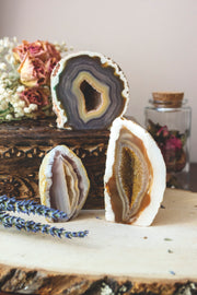 Three base cut agate stones displayed two on one row and one above. Varying in color from blue to brown.