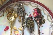 Variety of crystal spoons laid on a plate. Gold, silver, pewter, and brass.