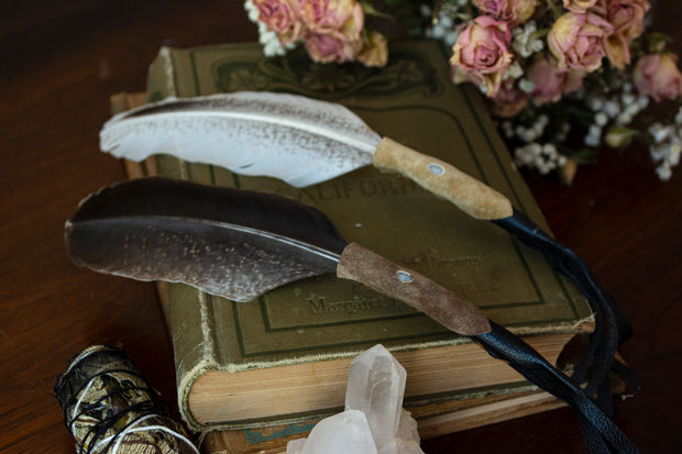 Two leather wrapped smudge feathers displayed on a book.