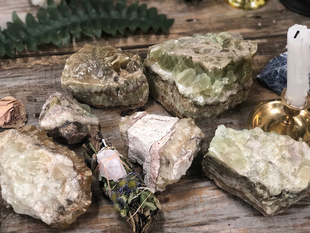 Multiple Green Calcite pieces on display.