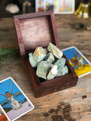 Wooden box filled with stones flanked by tarot cards.