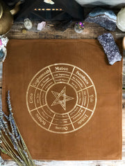 Close up of the Wheel of the Year Altar Cloth. Brown with gold lettering.