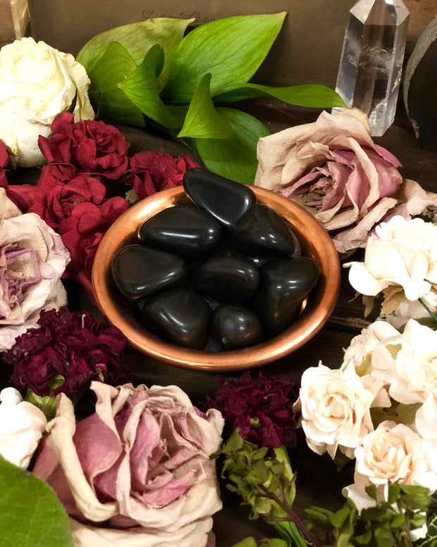 Bowl of polished black agate surrounded by flowers.