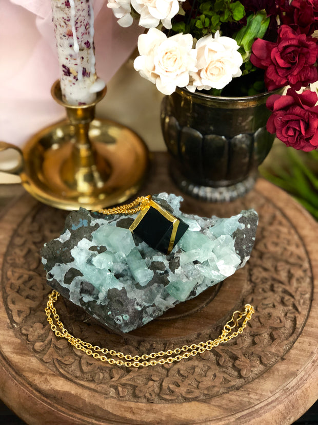 Square black jasper necklace with a gold chain displayed on a large crystal.