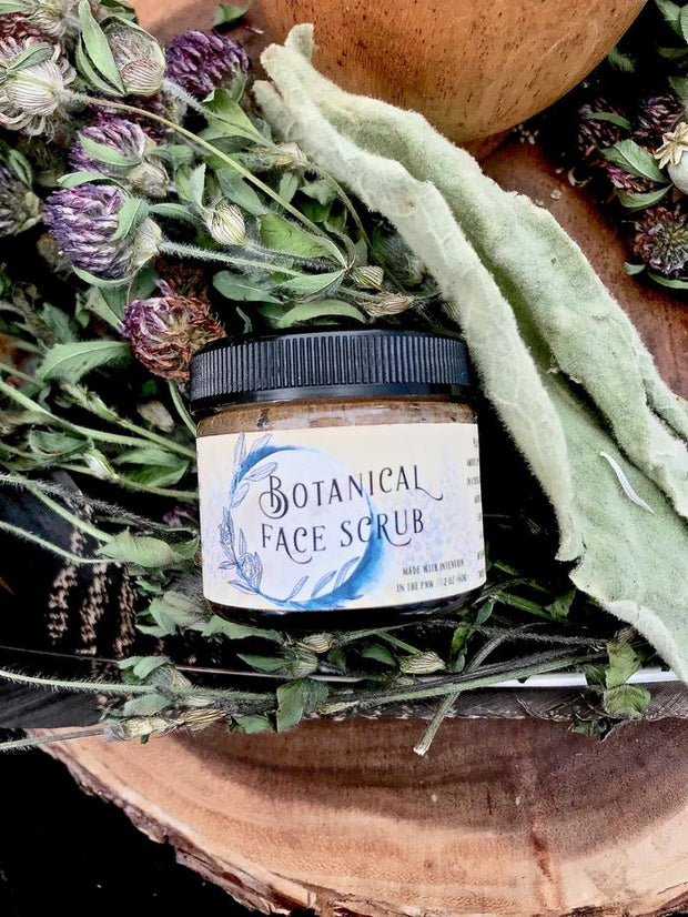 Facial scrub displayed on a bed of flowers.