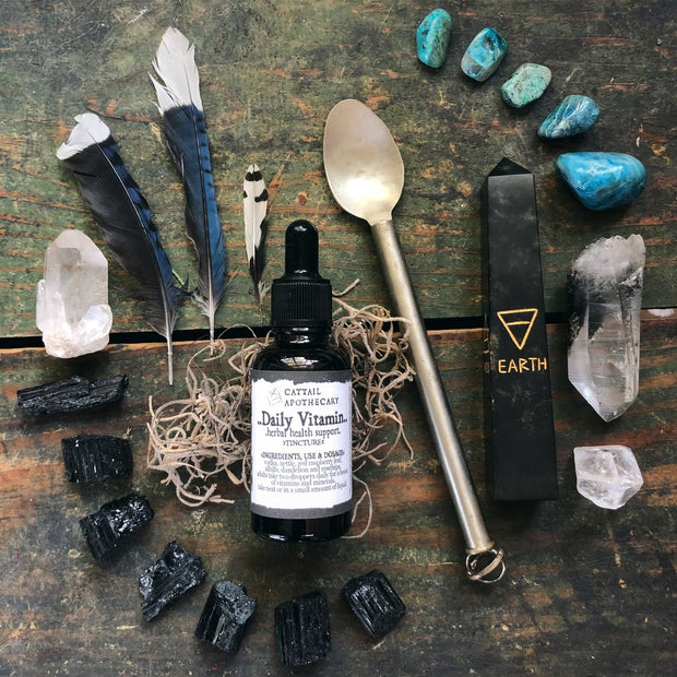 A daily vitamin glass bottle surrounded by witchy items.