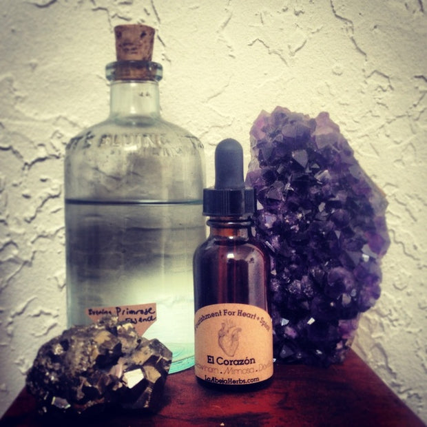 Glass bottle of El Corazon Tincture with amethyst on display behind it.