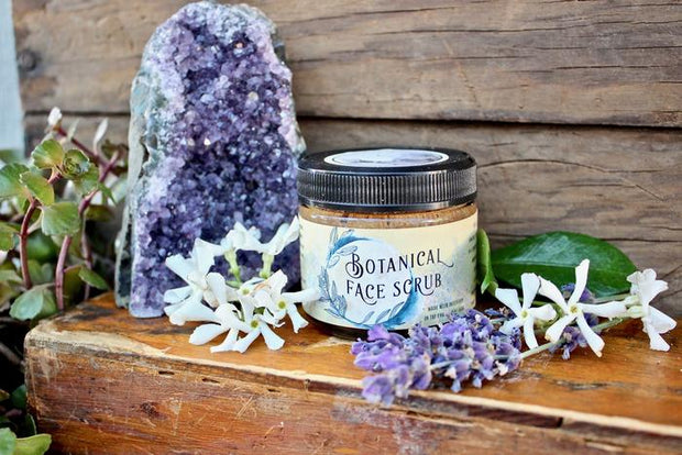 Purple flowers and crystals arranged around a tub of facial scrub.