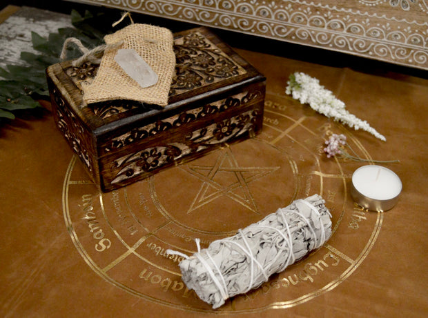 Clear Quartz on a brown bag set on top of a wooden flower carved box. A white sage bundle next to a white teacup candle arranged on a brown altar cloth.