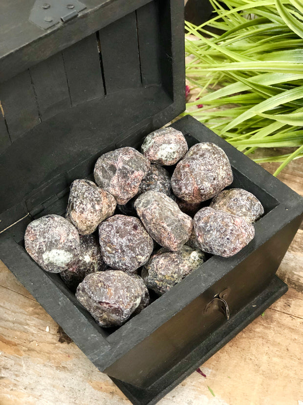 Wooden box filled with rough garnet.