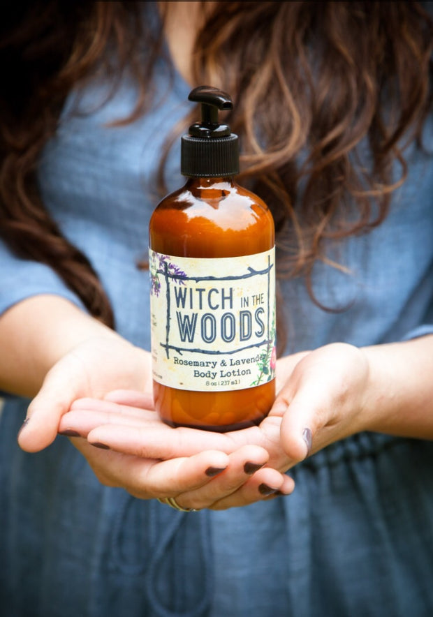 Lotion bottle held in two hands as to display the label Witch in the Woods.