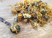 Loose calendula on a table and in a spoon.