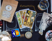 black cloth background with three tarot cards, sun and moon tile, and herbs in a bag on top