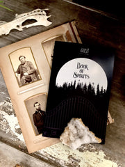 Cover of book of spirits displayed with old photos in the background.