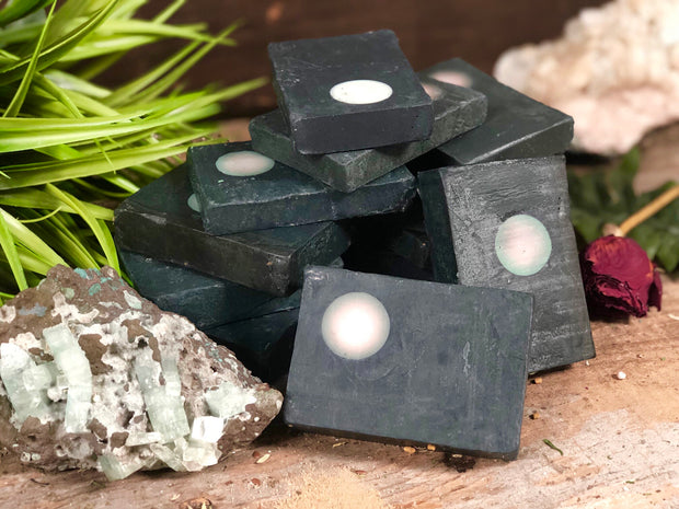 A stack of black soap with a white moon displayed with rocks and plants.