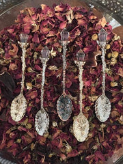 Close up of five different tea spoons with a single crystal on top