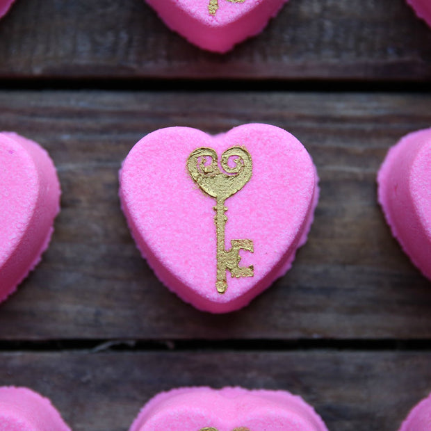 Pink heart shaped bath bomb with a golden key printed on top.