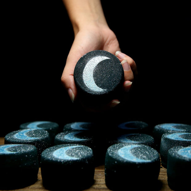 Black bath bomb with silver moon being held by a human hand.