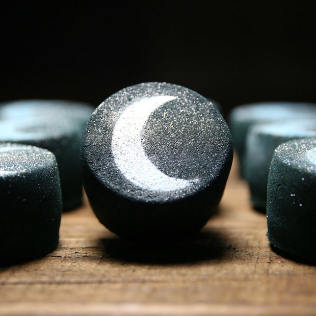 Black bath bomb with image of a silver crescent moon.