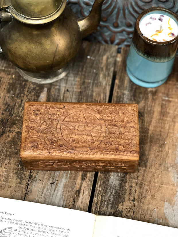 Wooden boxes carved with a pentagram on the lid.