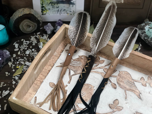 Three leather wrapped smudge feathers displayed on a book.