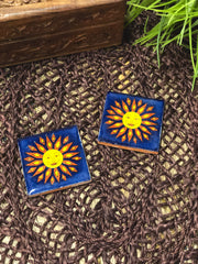 Two sun tiles displayed flat on brown lace.