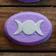 Purple oval bath bomb with the silver triple crescent moon pressed on its top.