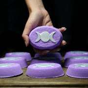 A hand holding a purple oval bath bomb with the silver triple crescent moon pressed on its top.
