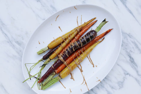Roasted with carrots on a white plate drizzled with JEM Organics nut butter