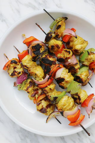 Curry chicken skewers with peppers and onions on a white plate
