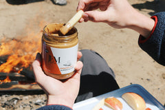 Dipping apple slice in JEM Organics nut butter by a fire pit