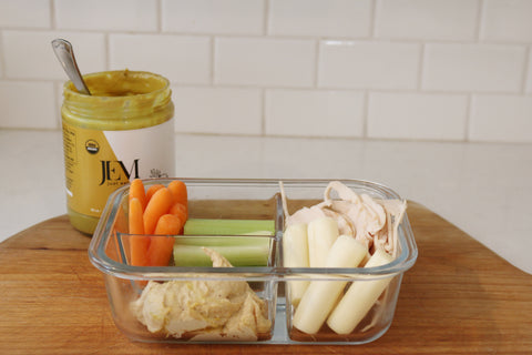 Tupperware filled with carrots, celery, turkey, cheese and nut butter
