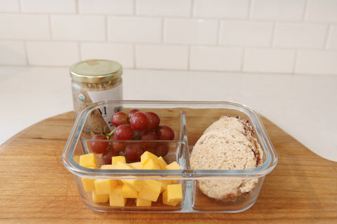 Tupperware filled with grapes, cheese and bread