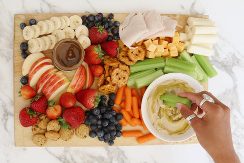 snack board filled with fruits and vegetables