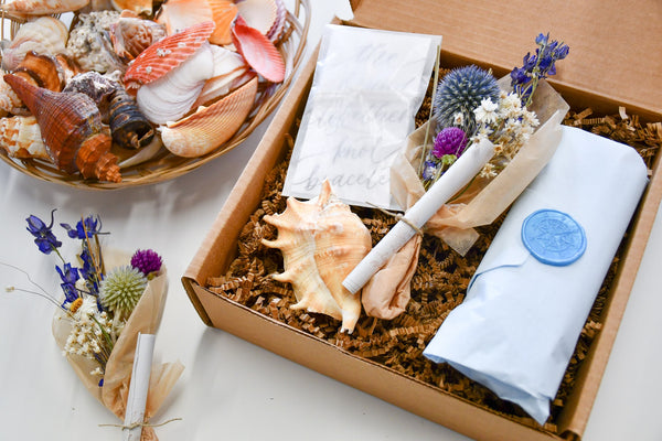 sailormade message in a bottle with calligraphy note, bouquet of dried flowers, true lovers knot bracelet and sea shell