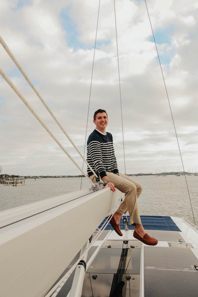 Paul Landry wearing brooks brothers on the boom of a sailing yacht
