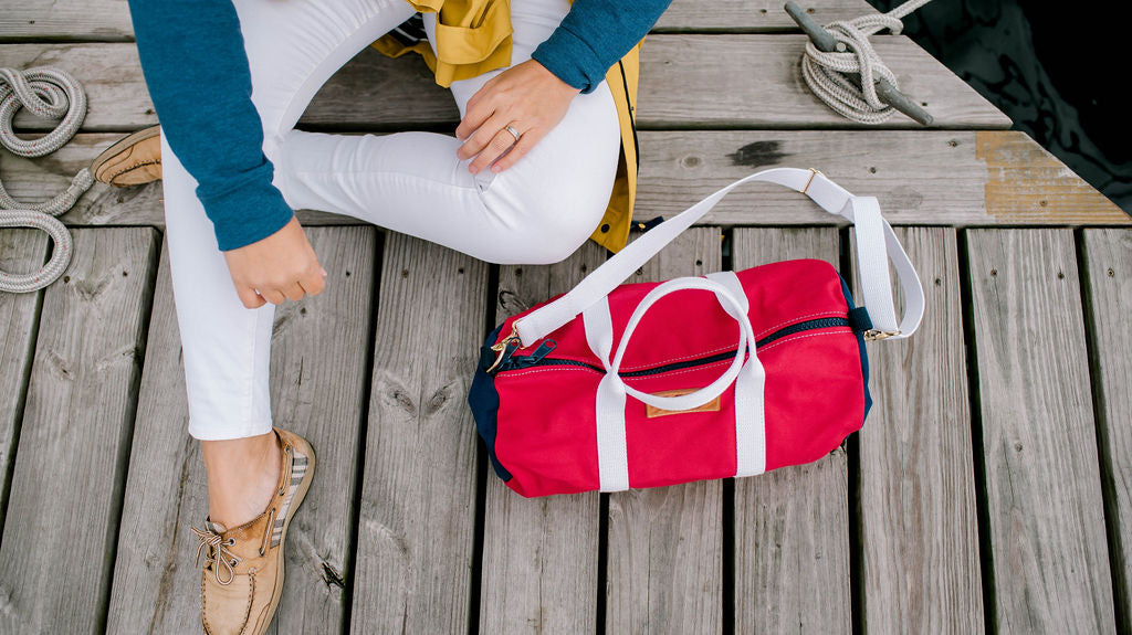 paul landry co sailing duffle bag on a boardwalk with boat shoes