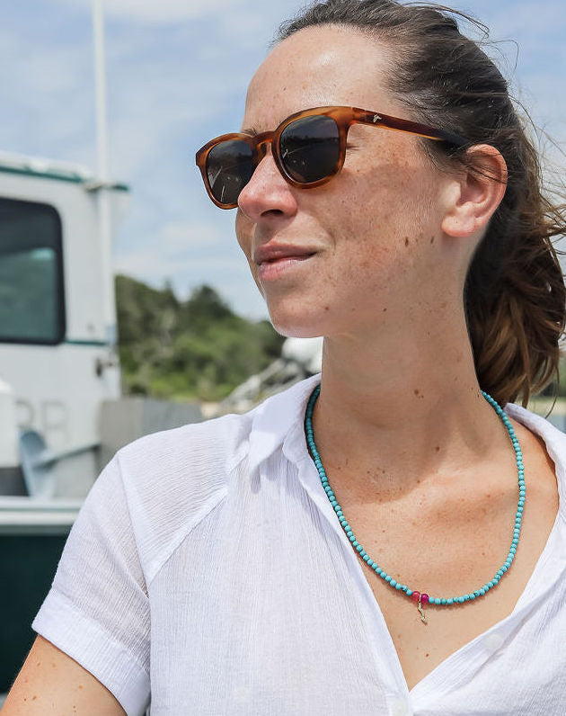 sailormade rayminder uv awareness necklace in turquoise worn outside on boat