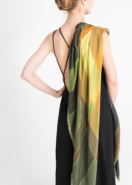 Model's back with Alba Amicorum's Aerial Weave scarf draped over the shoulder. It is styled with a black crisscross backed black dress. Scarf has autumnal, green, rust and warm yellow hues in a fluid weave pattern.