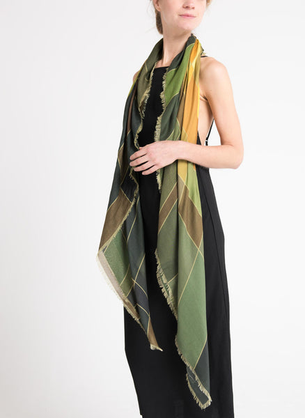 Model wearing a limited edition scarf by Alba Amicorum, named Aerial Weave. Draped long around the neck. It is styled with a black dress. Scarf has autumnal, green, rust and warm yellow hues in a fluid weave pattern.