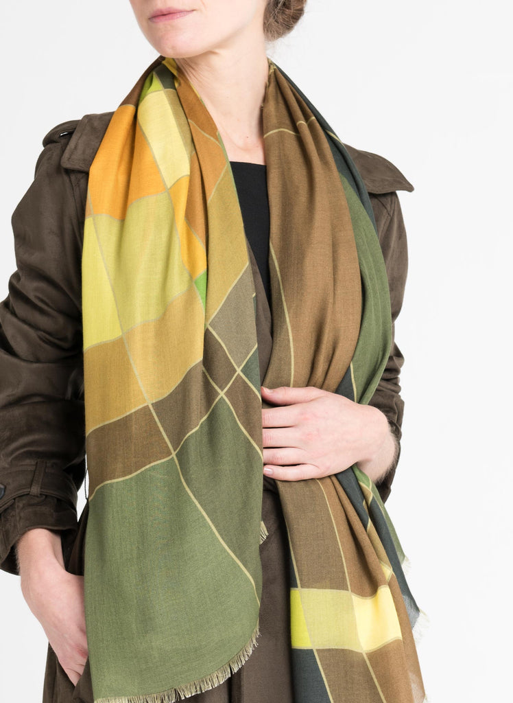 Model wearing a limited edition scarf by Alba Amicorum, named Aerial Weave. Draped long around the neck. It is styled with a brown trench coat. Scarf has autumnal, green, brown and warm yellow hues in a fluid weave pattern.