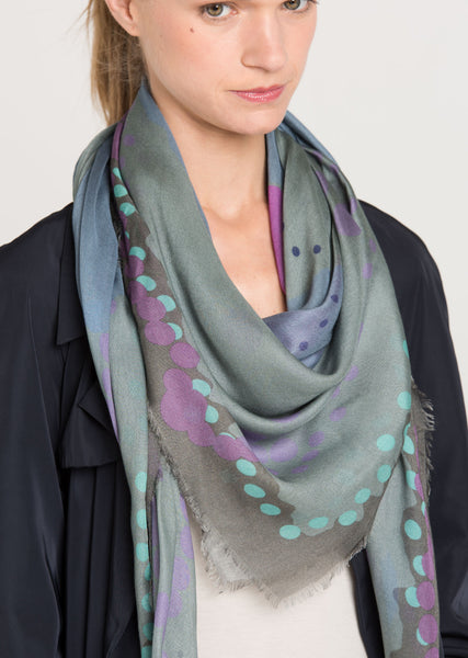 Limited edition scarf in subtle hues of muted grey-greens, mauves and slate blues in varying sizes of dots and circles on a soft light fabric. Close up of the model with the scarf draped around the neck over a navy trench. Alba Amicorum's Ascending space...
